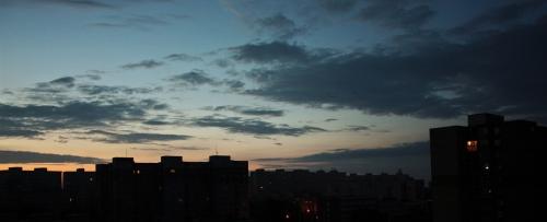 Východ slnka za petržalskými panelákmi. Brieždenie v Bratislave.